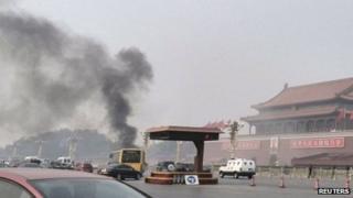 Vehicles travel along Chang'an Avenue as smoke rises at Tiananmen Square in Beijing, China, 28 October 2013