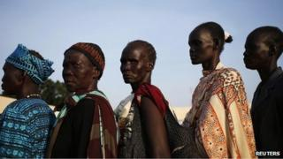 Women wait to vote in front of a polling station located at a school during a referendum in the town of Abyei on 27 October 2013