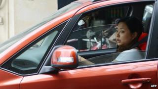 A woman drives her car on a street in Shanghai on October 30, 2013