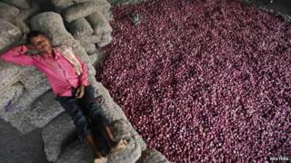 A labourer rests on sacks filled with onions at a wholesale vegetable market in the northern Indian city of Chandigarh October 24, 2013