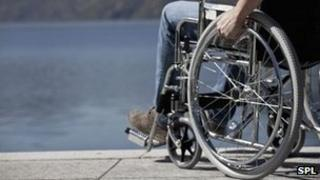 Man in wheelchair sitting by water anonymous disability