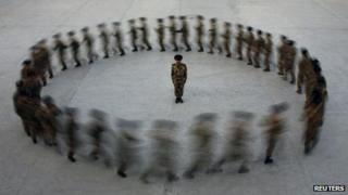Commander watches paramilitary police recruits run in a circle during training, Xinjiang (file photo - 28 August)