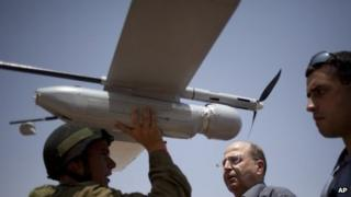 File image of an Israeli soldier holding up a 'Skylark' unmanned drone as part of a demonstration for Israel's Defence Minister Moshe Yaalon, centre, on 9 July 2013