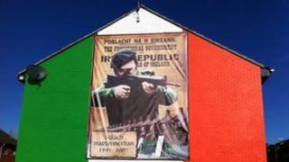 Banner featuring paramilitary gunman in Ardoyne in Belfast