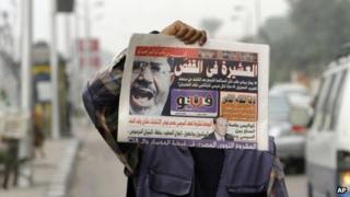 An Egyptian newspaper vendor displays a copy of a morning newspaper fronted by a picture of Egypt's ousted President Mohammed Morsi in Cairo