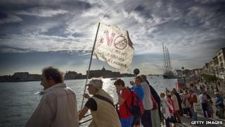 Protesters line the the bank of the Giudecca Canal during a demonstration to block a cruise ship