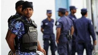 Maldives police stand guard during a protest of supporters of former Maldivian president and presidential candidate Mohamed Nasheed in Male on October 19, 2013.