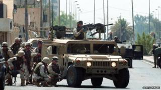 US troops take cover during a gun battle in Baghdad, 7 August 2003