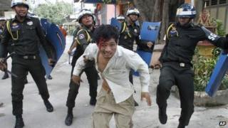 An injured Cambodian worker escapes from riot police in the compound of a Buddhist pagoda in Phnom Penh, Cambodia (12 November 2013)