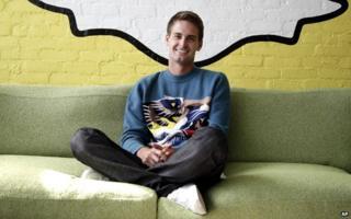 Evan Spiegel sits under the Snapchat logo