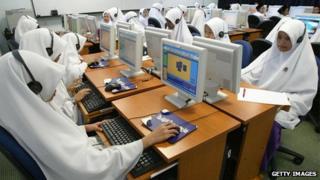 Singaporean women wearing hijabs sitting at computers
