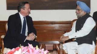 India's Prime Minister Manmohan Singh speaks with British Prime Minister David Cameron in Delhi