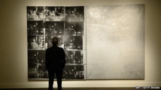 A man looks at Andy Warhol's Silver Car Crash painting