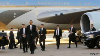 President Barack Obama is surrounded by US Secret Service agents after arriving at Dallas Love Field in Texas on 6 November 2013
