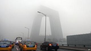 This picture taken on 5 June 2013 shows vehicles under heavy smog in Beijing
