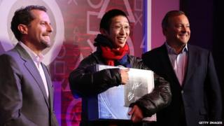 Andrew House, President and CEO, Sony Computer Entertainment, and Jack Tretton, President and CEO Sony Computer Entertainment America, present 24-year-old Joey Chiu of Brooklyn with the first of 444 PS4s to be sold at the PlayStation 4 North American Official Launch event