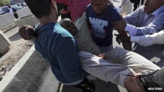 People carry a man who injured when Libyan militiamen opened fire into a crowd of protesters in Tripoli 15 November, 2013