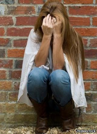 Woman with face in her hands beside a wall, stock image