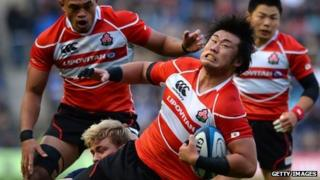 Shinya Makabe of Japan is tackled