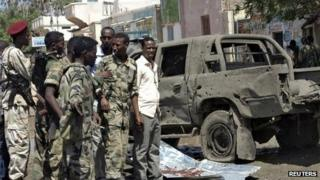 Somali policemen stand next to a damaged car at the scene of an explosion in Beledweyne in central Somalia, 19 November 2013