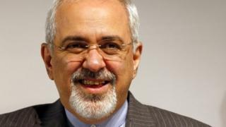 Iranian Foreign Minister Mohammad Javad Zarif smiles during a news conference after nuclear talks at the United Nations European headquarters in Geneva November 10, 2013.