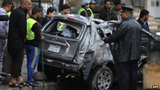 Iraqis inspect a damage car after a bomb attack in Baghdad's Karrada district (20 November 2013)