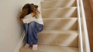 Child sitting on the stairs looking upset