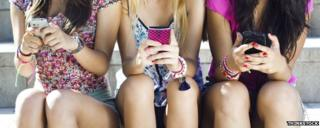 Girls sitting in a row using mobile phones
