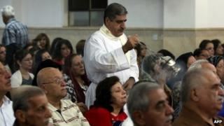 Iraqi Christians attend mass at the Mother of Continuous Aid Church in the Christian village of Ankawa, near the northern Kurdish city of Irbil, on 22 October 2013