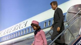 John F Kennedy and Jacqueline Kennedy descend the stairs of Air Force One in Dallas, 22 November 1963