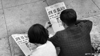 Two people in a Washington, DC, park read news of John F Kennedy's assassination.