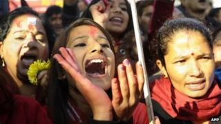 """Nepali Congress and Communist Party of Nepal (Unified Marxist-Leninist) (CPN-UML) supporters chant slogans at a rally celebrating the party""""s election result outside of a vote counting centre in Kathmandu on November 22, 2013."""