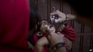 A Pakistani child receives a polio vaccine
