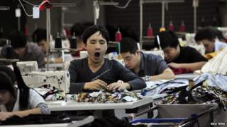 An employee yawns as he works at a garment factory in Humen township, Guangdong province, 24 November 2013