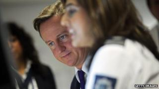 UK Prime Minister David Cameron watches security monitors as he talks to UK border agency officials in their control room during a visit to Heathrow terminal 5 (October 2011)