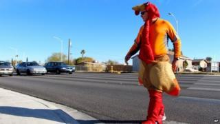 Man in turkey costume crosses the road