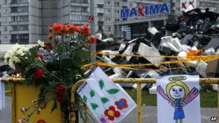 Paintings hang on a fence in front of the Maxima supermarket in Riga, Latvia, Sunday, Nov. 24, 2013