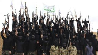Islamist fighters dressed in black with rifles