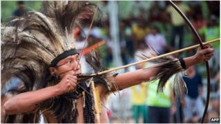 Man of the Terena ethnic group uses bow and arrow in Brazil