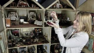 Woman examining some of the items in the dolls house