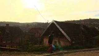 A man walks across a road in Transylvania, Romania