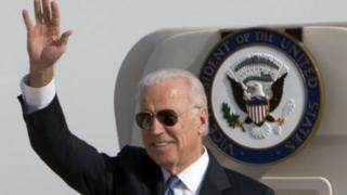 U.S. Vice President Joe Biden waves as he walks out of Air Force Two at the airport in Beijing, China, Wednesday, Dec. 4, 2013.