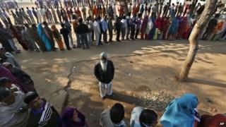 Indian voters wait in queues to cast their votes for the Delhi state election in New Delhi, India, Wednesday, Dec. 4, 2013