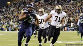 Seattle Seahawks defensive end Michael Bennett (left) runs the ball for a touchdown during a game at CenturyLink Field in Seattle, Washington, on 2 December 2013