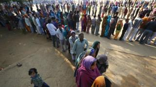 Indian voters wait in queues to cast their votes for the Delhi state election in New Delhi, India, Wednesday, Dec. 4, 2013.