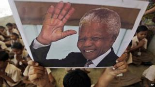 Boy holding up picture of Nelson Mandela