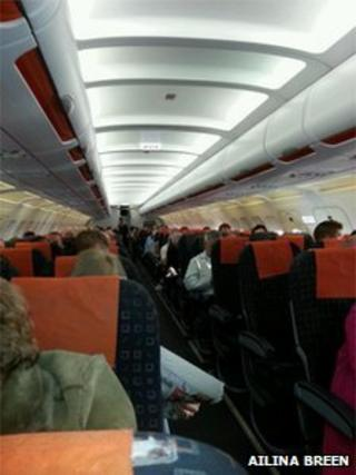 Passengers sit on a plane at Belfast International Airport waiting for their flight to take off