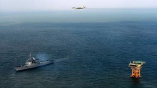 This picture taken on December 2, 2013 shows the South Korean Navy patrol-aircraft P-3C and South Korean Aegis DDG-992 during defence operations near Ieodo Ocean Research Station.