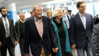 Korean War veteran Merrill Newman (C-L), 85, walks with his wife Lee (C-R) and son Jeff (R) after arriving at San Francisco International Airport on December 7, 2013 following his release from detention in North Korea
