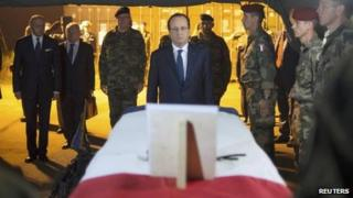 French President Francois Hollande pays tribute near a flag-draped coffin bearing one of two French soldiers killed in Bangui